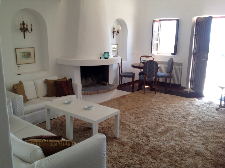 The living room is spacious, airy and high ceilinged. Fitted with two couches (2 place and 3 place), a rotunda dining table with four period chairs, a semi-elliptic fireplace and wall-to-wall carpeting