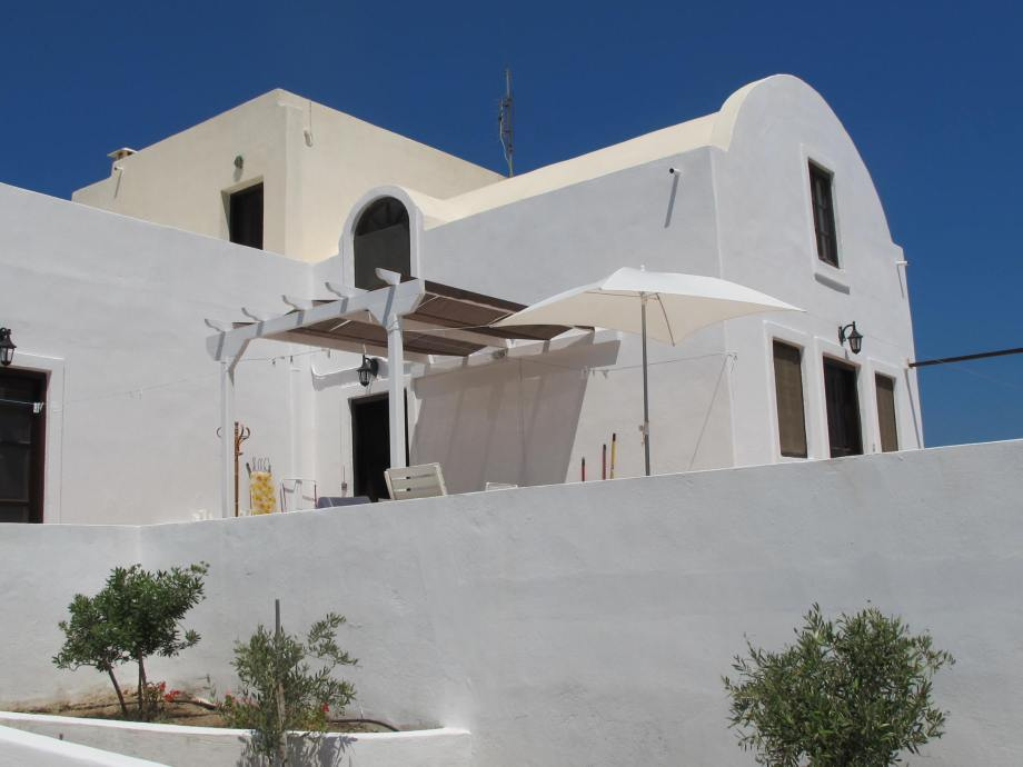 Partial view of the villa showing the main entrance and the two verandas. The architectural style is distinctive Santorinian!