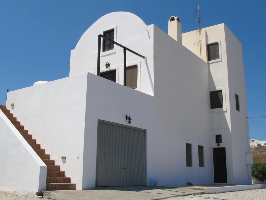 The villa as seen from the driveway. Showing the garage entrance, further in the entrance of the independent suite as well as the external stairway leading to the main area of the three-storied villa