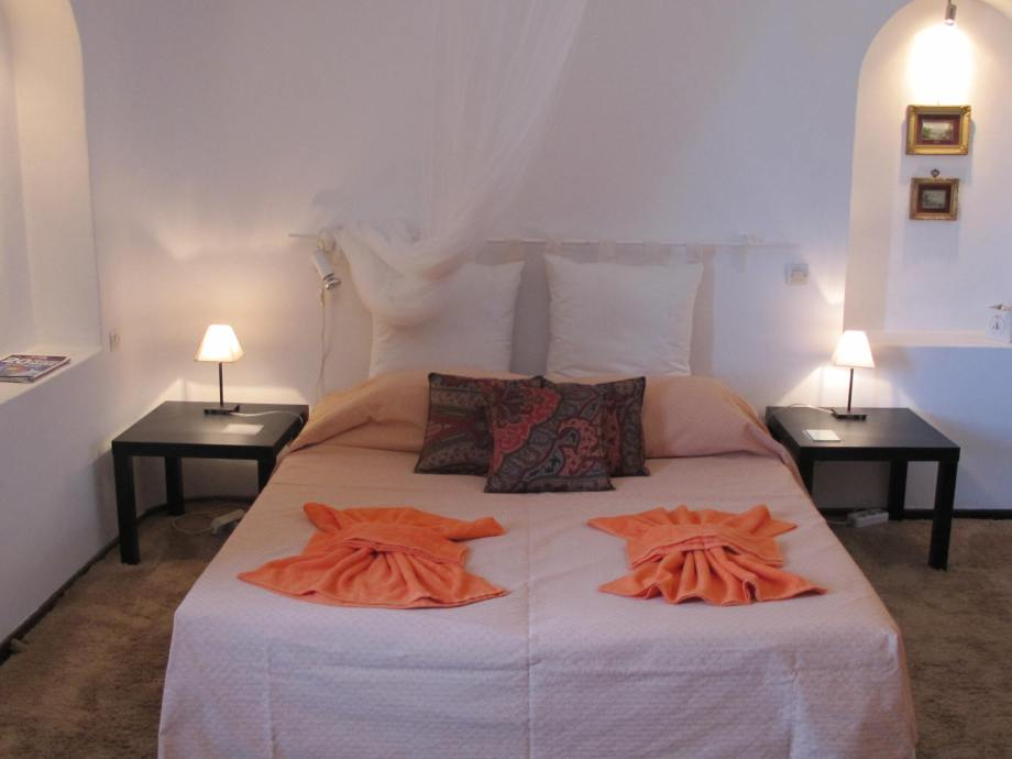 The master bedroom is fitted with a king sized bed and comfortable head pillows and reading lights on each side